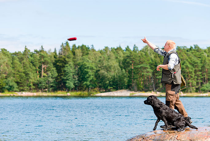 A man throwing a toy into a lake whilst a dog chases